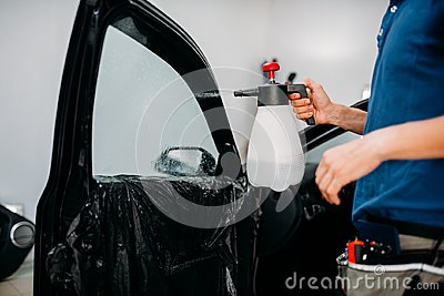 Male hand with spray, car window tint installation