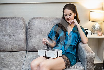 Young beautiful woman in lingerie with gift in hand on sofa