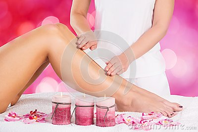 Beautician Waxing Leg Of Woman With Wax Strip
