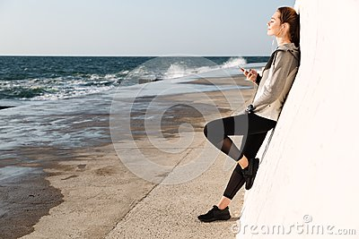Full-length photo of young charming woman in sport wear listening to music with closed eyes, standing near white wall, seaside