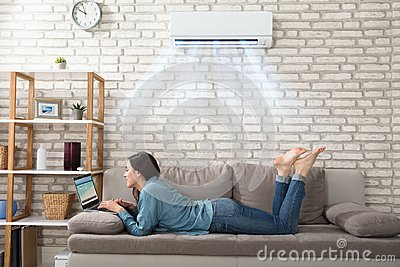 Woman Using Laptop Under The Air Conditioner