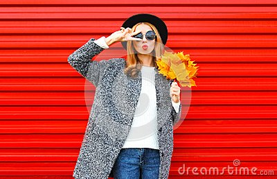 Fashion autumn young woman with red lips and yellow maple leaves