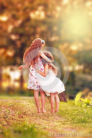 Two Happy little girl embracing and smiling at summer day, back