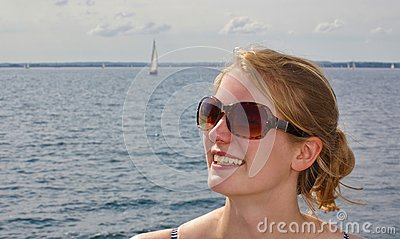 Portrait of a beautiful young woman wearing sunglasses with the sea and a distant sailboat in the background