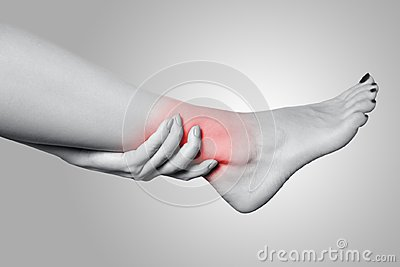 Closeup view of a young woman with pain on leg on gray background.