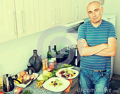 Positive guy stands proudly in kitchen hands clasped