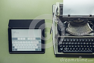 Analog and digital typewriters lie on the green surface. Continuity of generations, technology development concept