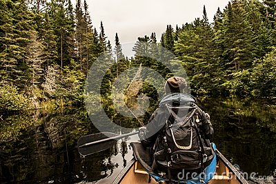 Girl canoeing with Canoe on the lake of two rivers in the algonquin national park in Ontario Canada on cloudy day