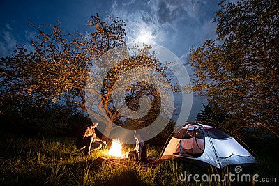 Romantic couple tourists sitting at a campfire near tent under trees and night sky with the moon