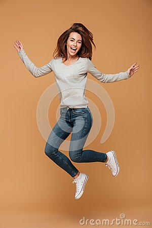 Full length photo of charming young woman in casual wear jumping