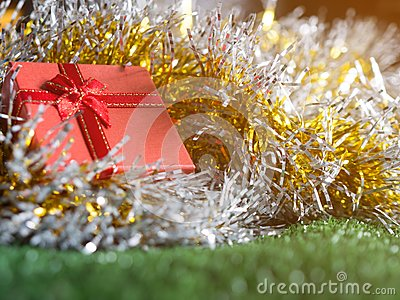 Red gift box with red ribbon bow and golden seam place on silver and gold rainbow glowing decoration background on green grass.