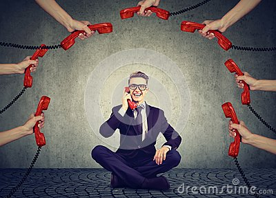 Business communications customer support concept. Businessman always on the telephone answering many phone calls