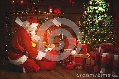 Merry Christmas! santa claus near the fireplace and tree with gi