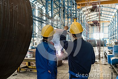 Two Asian experts talking while supervising fabrication