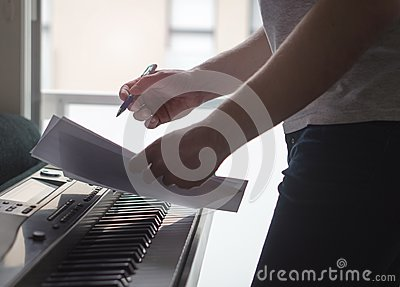 Musician brainstorming and innovating new song ideas at piano