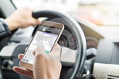 Texting while driving car. Irresponsible man sending sms.