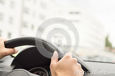 Man driving car in city. Driver holding steering wheel.