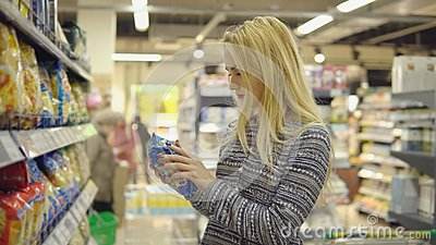 Woman in a supermarket standing in front of the freezer and choose buying pasta product.
