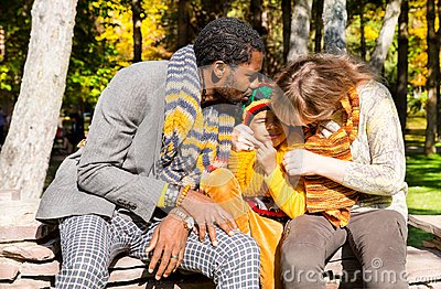 Happy family in autumn park. African American family: black father, mom and child boy on nature in fall.