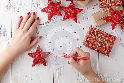 Hand pointing December 25 in a calendar surrounded by Christmas ornaments
