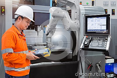 stock image of maintenance engineer programming automatic robotic hand with cnc machine in smart factory. industry 4.0 concept