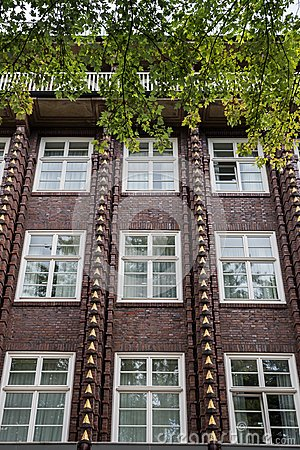 Facade of red brick Building with golden Ornaments and white Windows, Hamburg, Germany