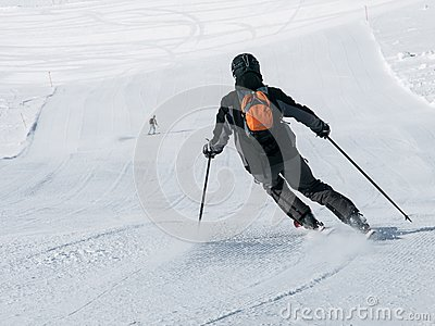 Skier in black downhill skiing on a ski slope. View from back