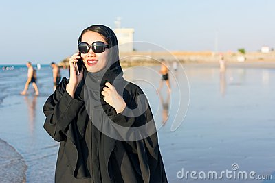 Woman in abaya using phone on the beach