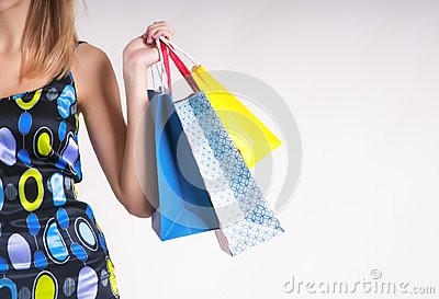 Young woman in summer shopping with shopping bags on gray background