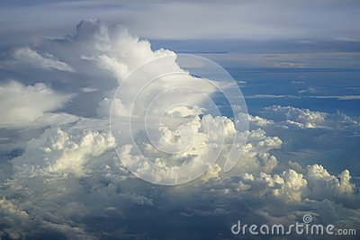 View of abstract dense soft fluffy white cloud  with shades of blue sky and earth background from above flying plane window