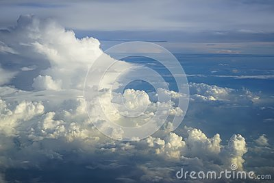 View of abstract dense soft fluffy white cloud copyspace with shades of blue sky and earth background from above flying airplane
