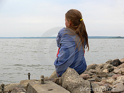 A girl sitting on the rocks by the beach
