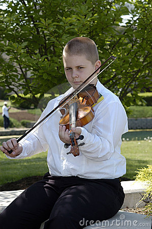 Boy sitting outside playing viola
