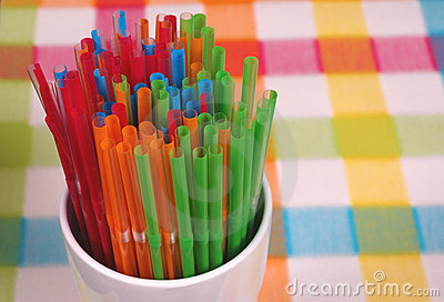 Colorful straws in white glass on checkered mat