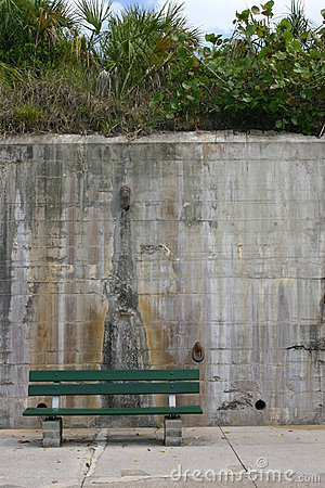 Green bench set against a tall concrete wall