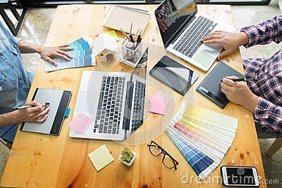 stock image of graphic design partners working together renovation and technology concept - on a desktop computer and selection using some color