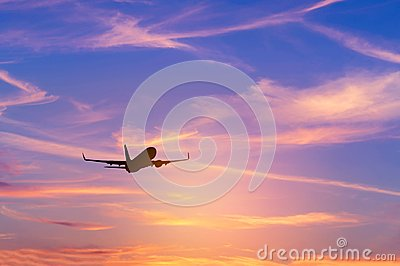 Silhouette passenger airplane flying away in to sky high altitude during sunset time