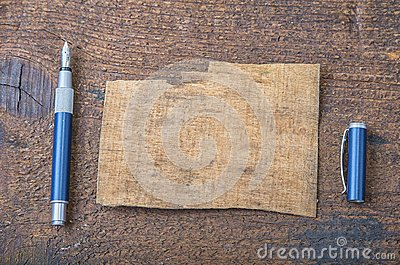 Torn piece of old paper for message or word of wisdom with pen on brown wood