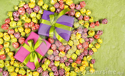 Gifts and sweets. Celebratory background. Multicolored popcorn and gift boxes