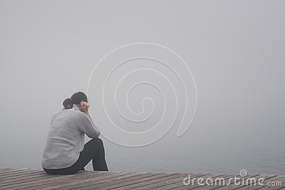 Despair young woman sits lonely at the edge of a wooden path of a bridge bent and sadly lost in thought in the fog