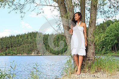 Pretty girl leaning on tree by Dam Rimov