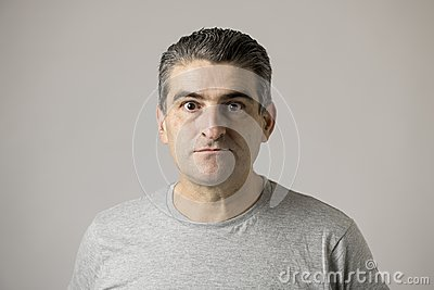 Unattractive 40s or 50s white funny man in sick and mad strange face expression isolated on grey background