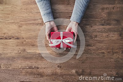 Woman hands in gray sweater on wood table giving red Christmas gift box wrapped with white ribbon