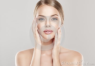 Portrait of young woman with clean fresh skin and soft, delicate make up. Woman  is touching tenderly to own face.