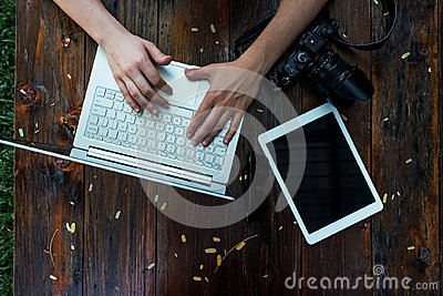 Laptop, camera on wooden background. Flat lay of working place of freelancer or individual entrepreneur