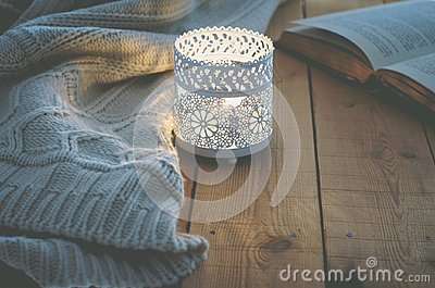 Lit Candle White Knitted Sweater Open Book on Plank Wood Table by Window. Cozy Winter Autumn Evening. Natural Light