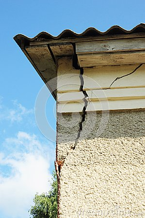 Damaged house stucco wall corner. Cracked Wall near Roof Construction. detail of damaged house corner dilapidated old building