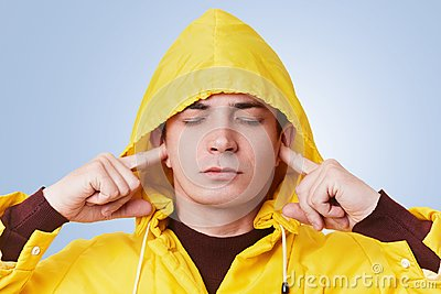Restful attractive male closes eyes and plugs ears, tries to concentrate and not hear loud noise, wears yellow hood on head, isola