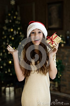 Emotional girl in santa hat with enthusiasm and joy and happiness keeps given to her New Year`s Christmas gift