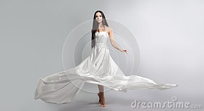 fashion photo of young girl in white dress flying tissue. Lightweight material.